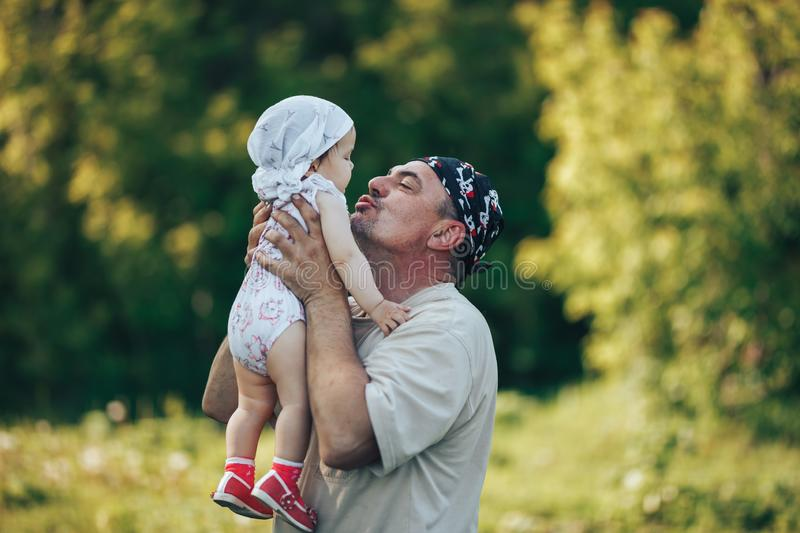 Young grandfather playing with adorable baby girl over a nature background. Grandparents and grandchild leisure time concept. Senior men playing with adorable royalty free stock photos