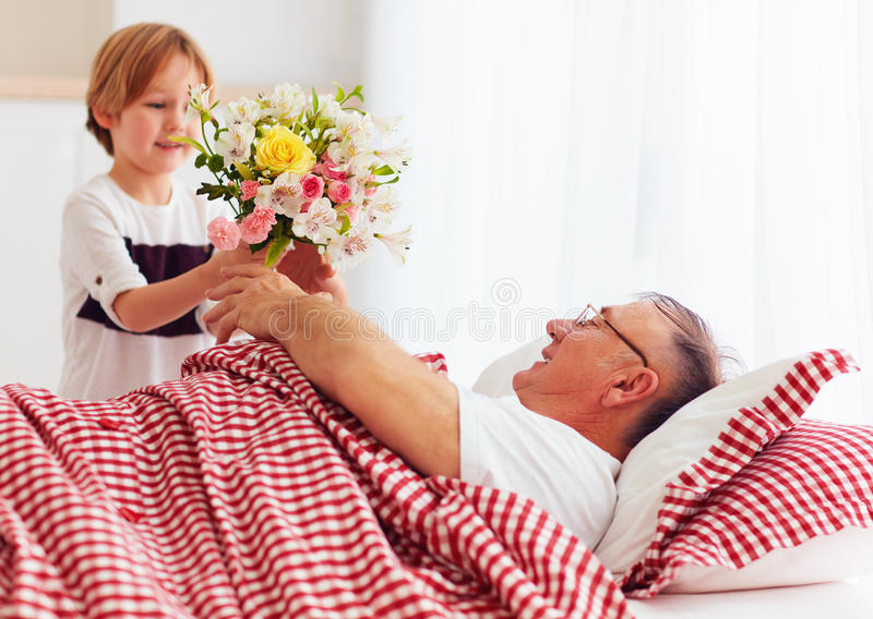 Young grandson with flower bouquet came to visit his sick grandpa in hospital ward. Young grandson, kid with flower bouquet came to visit his sick grandpa in royalty free stock photo