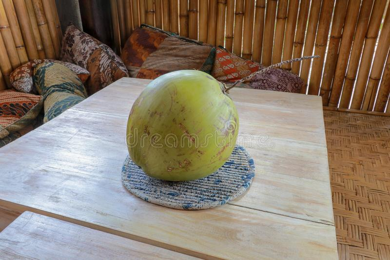 Young green coconut on teak table. Whole coconut with bamboo background and pillow. Healthy tropical fruit from coconut palm. stock image