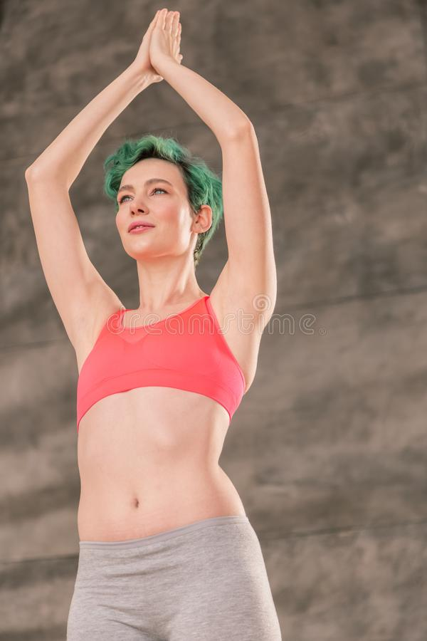 Young green-haired woman with nice abs doing yoga pose. Doing yoga pose. Young green-haired woman with nice abs feeling energized while doing yoga pose stock photos