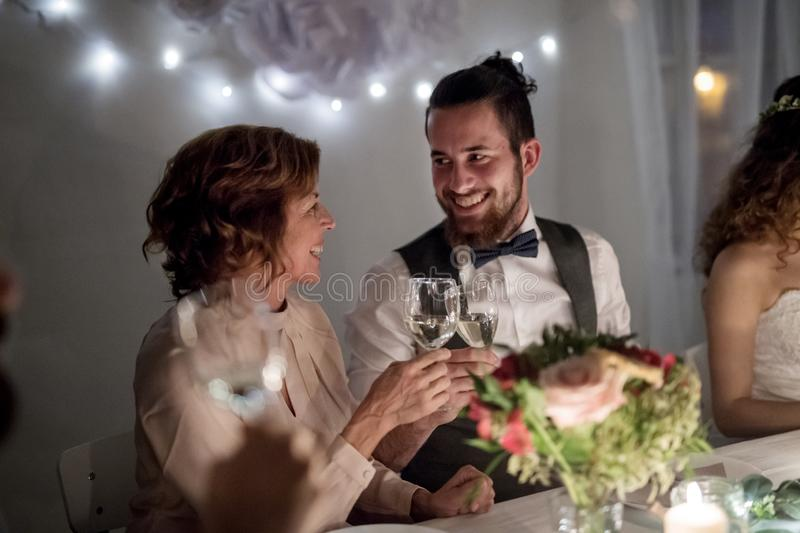 Young groom and his mother sitting at a table on a wedding, clinking glasses. stock images