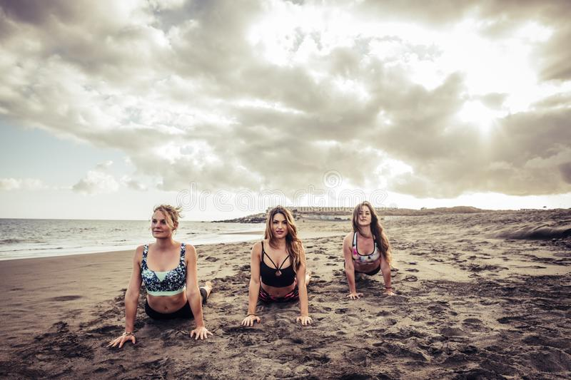 Young group beautiful women yoga practice on mat relaxation in class exercise with pose fitness sport for healthy on the beach and royalty free stock photo