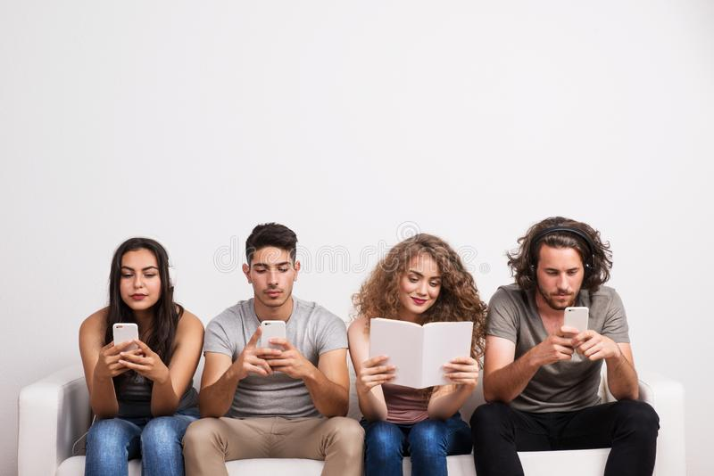 Young group of friends using modern technology and traditional source of information. stock images