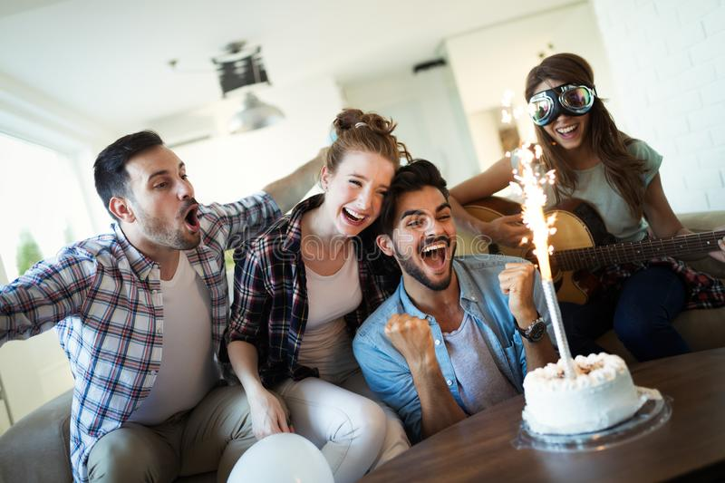 Young group of happy friends celebrating birthday. With cake stock photo