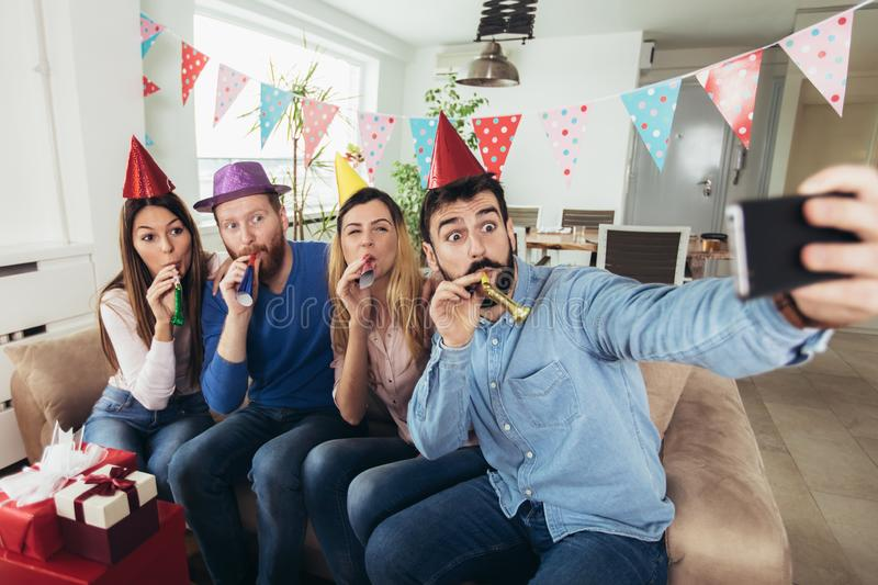 Happy friends celebrating birthday at home make selfie photo. Young group of happy friends celebrating birthday at home make selfie photo royalty free stock photos