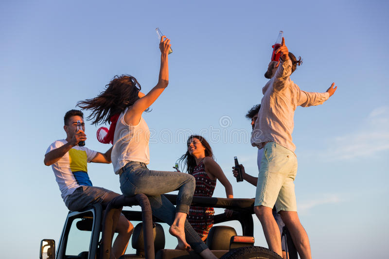 Young group having fun on the beach and dancing in a convertible car.  stock image