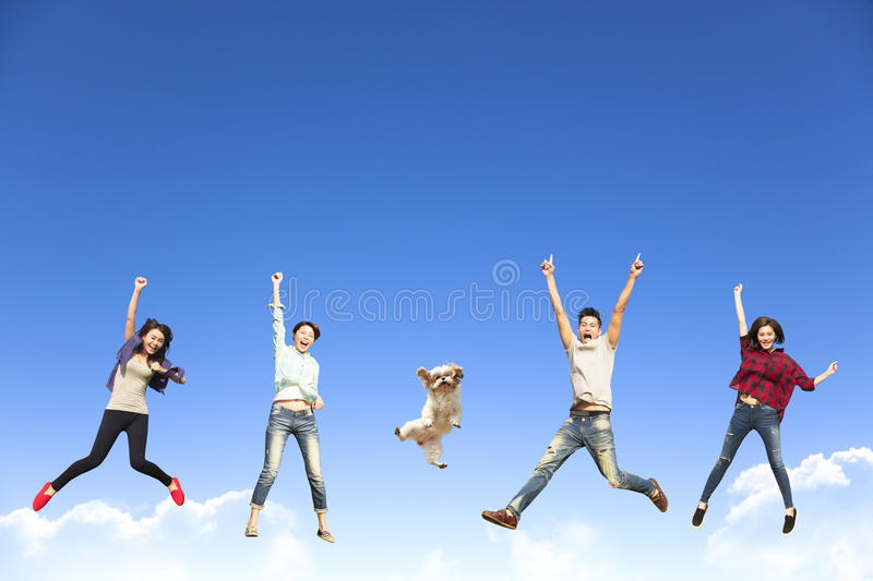 young group jumping together with dog stock images