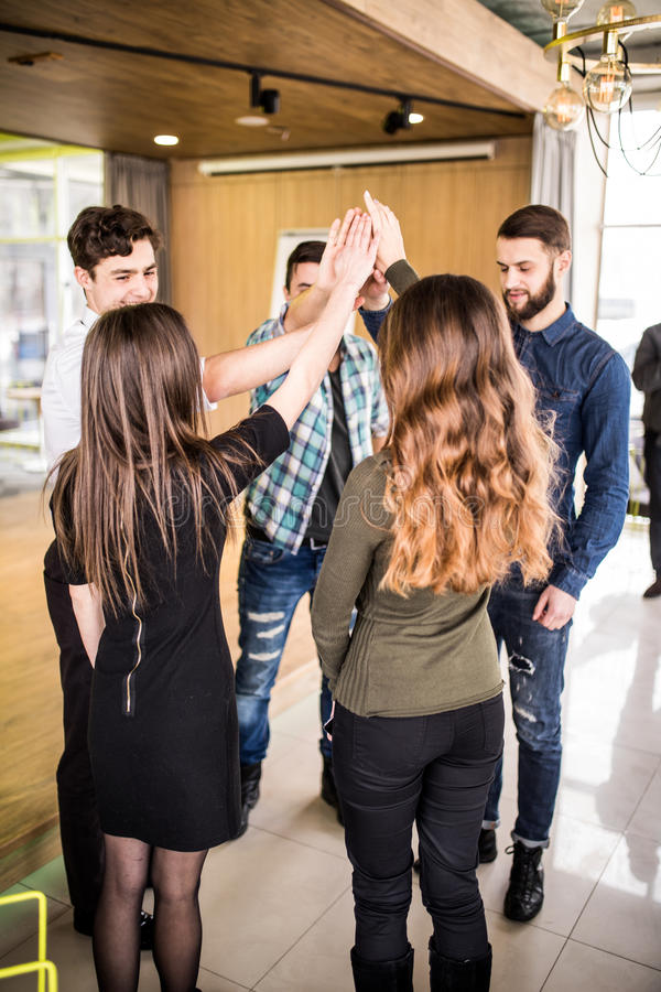 Young group of people high fiving each other at meeting or seminat of teamwork in office royalty free stock photo
