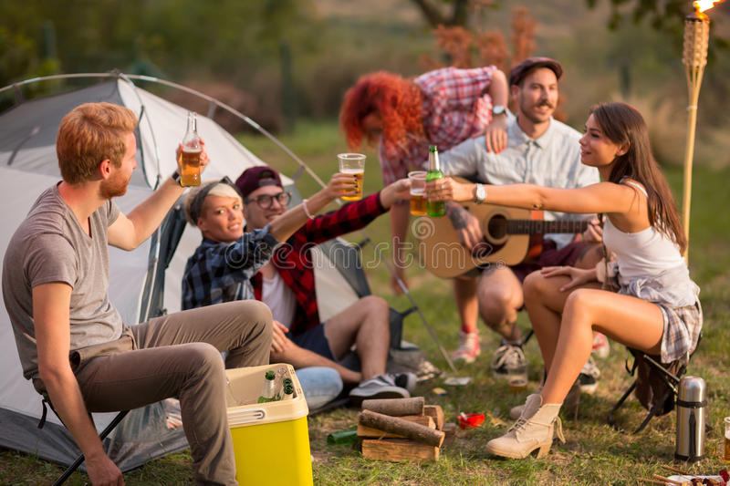 Young group toasting with bottles and glasses of beer in campground. On sunset in forest royalty free stock photo