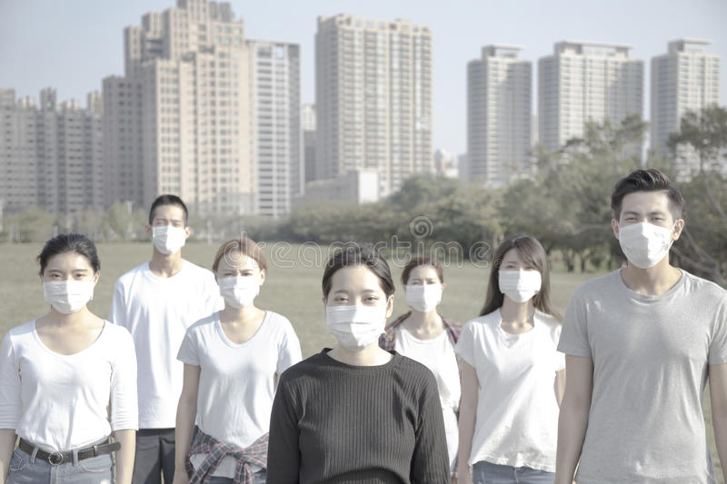 Young group wearing mouth mask against air pollution in city stock photos
