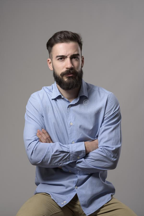 Young grumpy pessimistic bearded business man with crossed arms sitting and looking at camera. Against gray studio background royalty free stock images