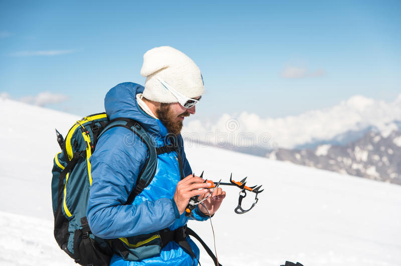 A young guide prepares crampons for use stock photos