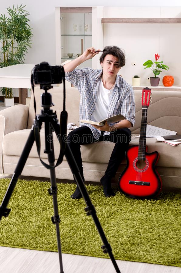 Young guitar player recording video for his blog royalty free stock image