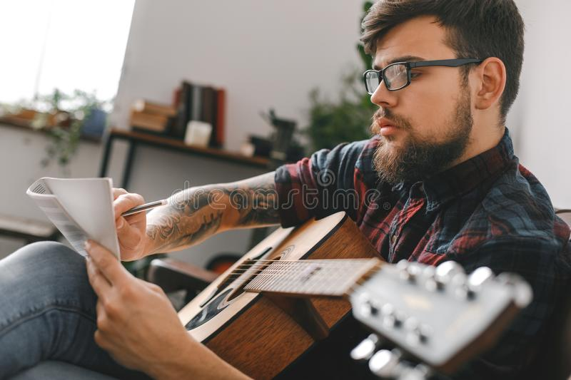 Young guitarist hipster at home with guitar sitting writing melody inspired stock images
