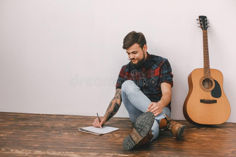 Young guitarist hipster at home with guitar sitting writing song. Young male guitarist hipster indoors with guitar sitting on the floor writing song smiling stock images