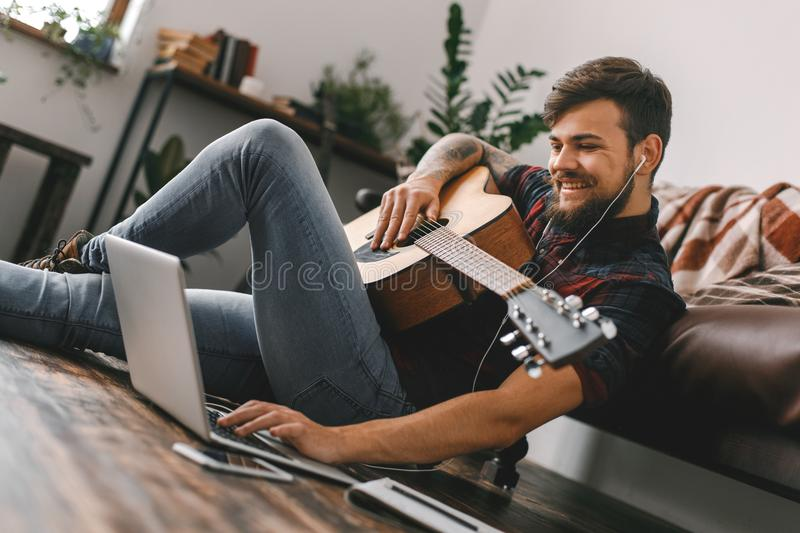 Young guitarist hipster at home sitting on the floor holding guitar earphones music browsing laptop. Young male guitarist hipster indoors holding guitar sitting stock photo