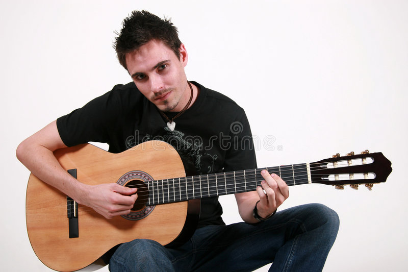 Young Guitarist - Jon. Young male guitarist playing an acoustic guitar royalty free stock image