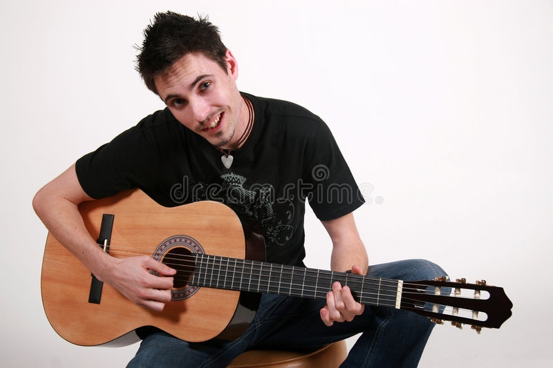 Young Guitarist - Jon. Young male guitarist playing an acoustic guitar royalty free stock images