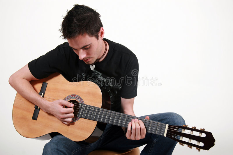 Young Guitarist - Jon. Young male guitarist playing an acoustic guitar stock photo