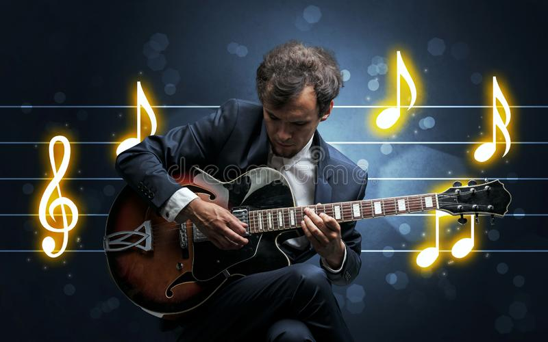 Young guitarist with music sheet. Young handsome guitarist playing with music sheet background royalty free stock photos