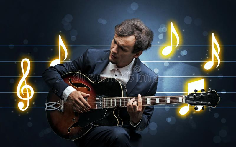 Young guitarist with music sheet. Young handsome guitarist playing with music sheet background stock image