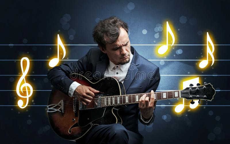 Young guitarist with music sheet. Young handsome guitarist playing with music sheet background stock photo