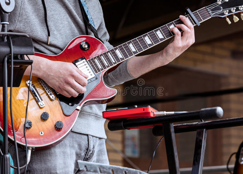 Young guitarist performing on outdoor stage during live concert royalty free stock image