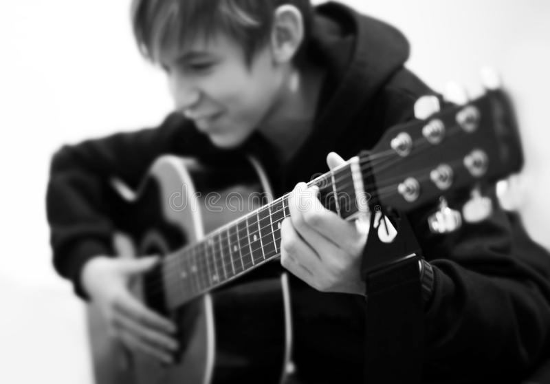 Young guitarist. Plays the acoustic guitar stock images