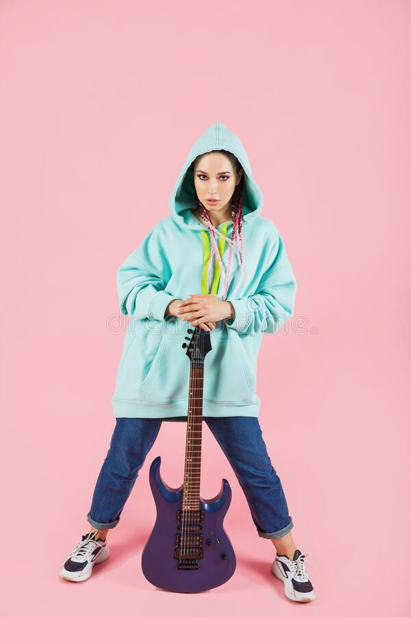 Free Young Guitarist Woman In Oversize Clothes With Electric Guitar Amp Isolated On Pink Background Stock Images - 173135404