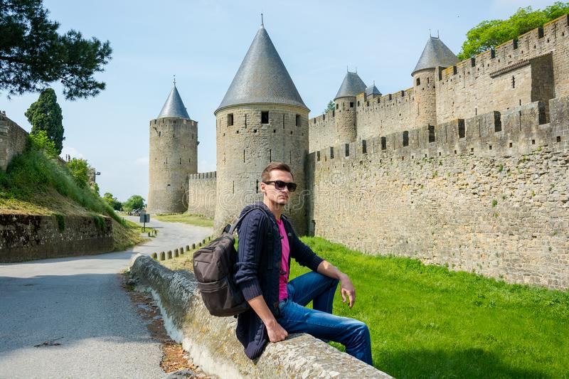 A young guy with backpack sits near fortress wall of the medieval city Carcassonne in France royalty free stock photography