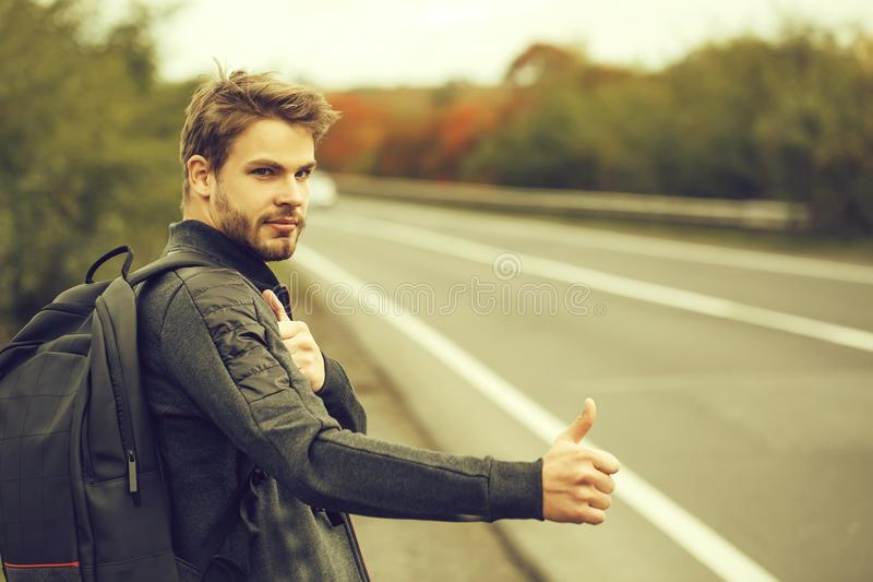 Young guy hitchhiking autostop. Young guy with beard on serious handsome face in casual clothes black backpack standing near road way hitchhiking autostop with royalty free stock photos