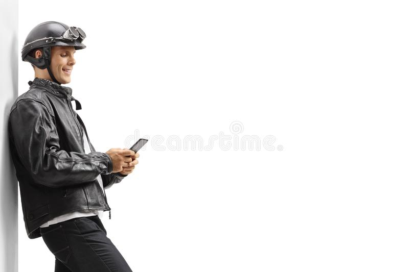 Young guy biker leaning against a wall and using a mobile phone royalty free stock photo