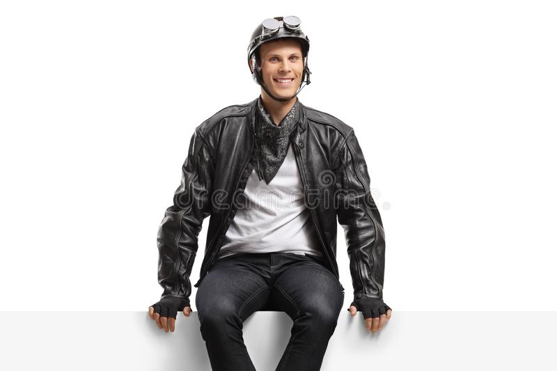 Young guy biker sitting on a panel and looking at the camera stock images