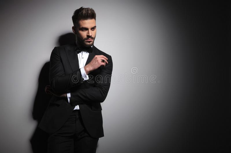 Young guy in black tuxedo holding arms folded. On gray studio background royalty free stock image