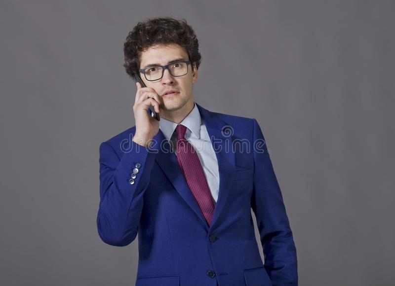 Young guy in blue jacket and glasses keeping his phone to ear stock images