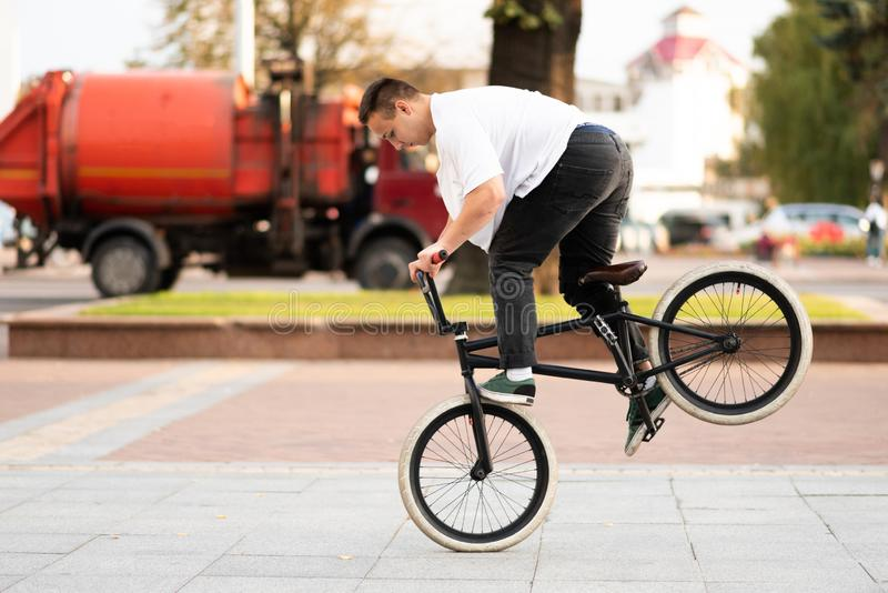 A young guy on a BMX bike, rides on the front wheel, braking with his foot royalty free stock photos