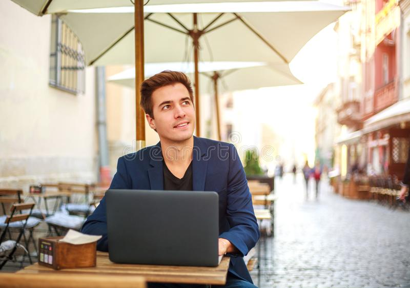 Young guy business man with laptop at table of summer cafe on street working outdoors stock images