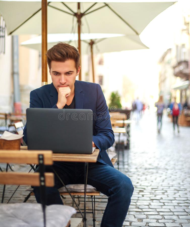 Free Young Guy Business Man With Laptop At Table Of Summer Cafe On Street Working Outdoors Royalty Free Stock Image - 163903416