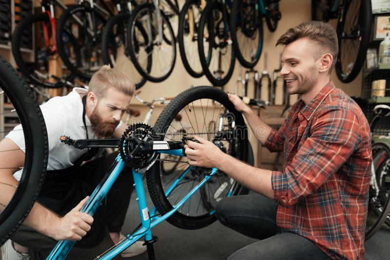 A young guy came to the workshop to repair his bicycle. royalty free stock photo