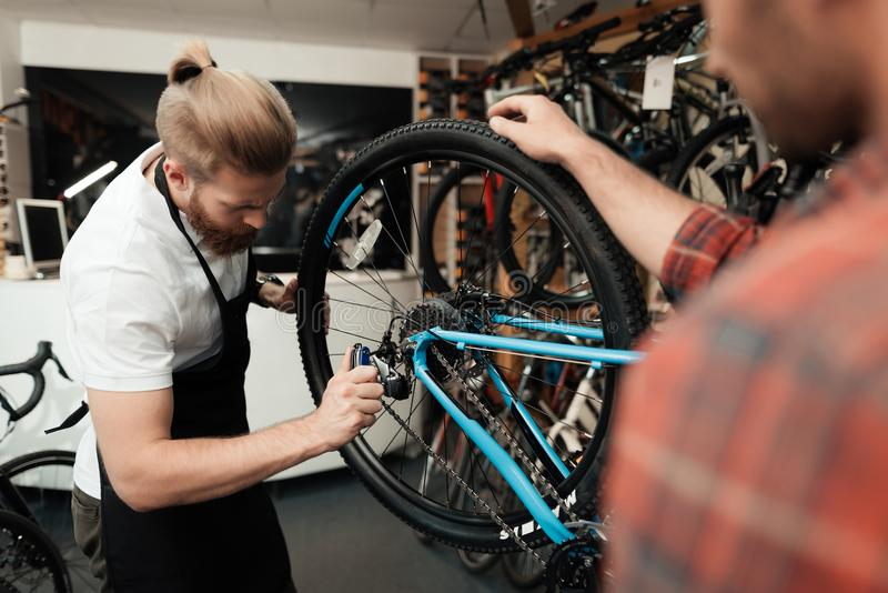 A young guy came to the workshop to repair his bicycle. stock photo