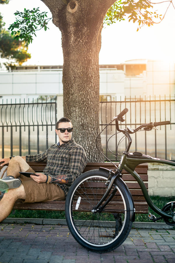 Young Guy Cyclist Resting On Bench And Using Tablet Communication Connection Digital Devices Technology Concept stock photo