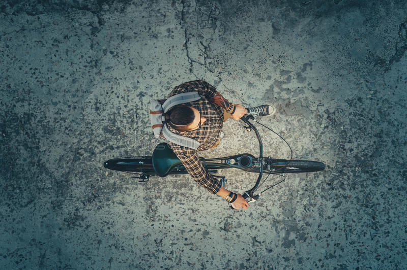 Young Guy Cyclist Riding On Bike Down The Street, Top View. Daily Lifestyle Urban Resting Concept. Young Man Cyclist In Glasses With Backpack Riding On Bike Down stock photo