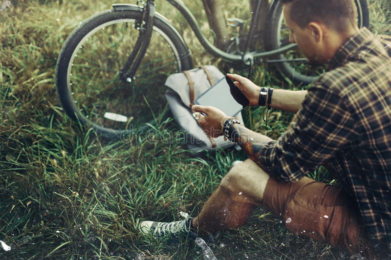 Young Guy Cyclist Sits On Summer Meadow Near Bicycle, Holding And Looking At Tablet Recreation Resting Travel Destination Concept stock photography