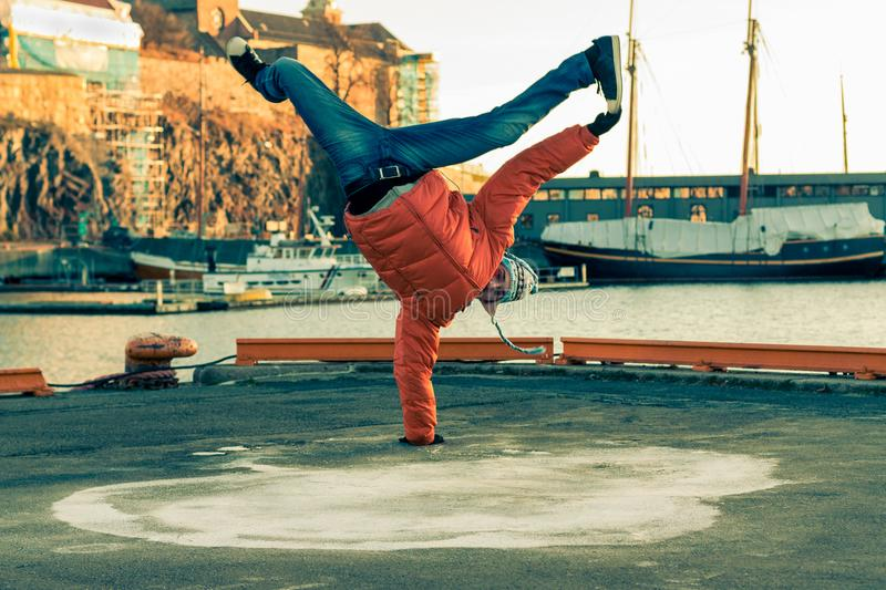 Young guy dancing break dance on the waterfront in an orange jacket in winter. stock images