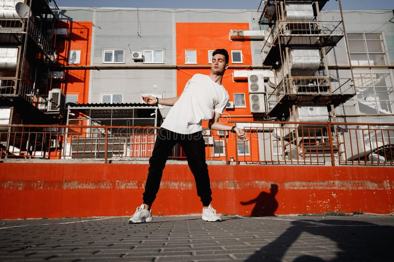 Young guy dressed in jeans and t-shirt is dancing modern dance in the street on the background of urban buildings in the stock images