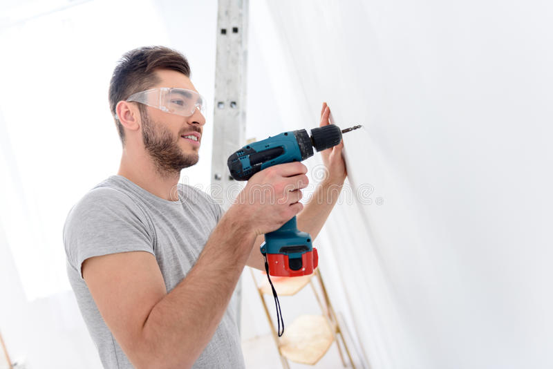 Young guy drilling white wall stock image