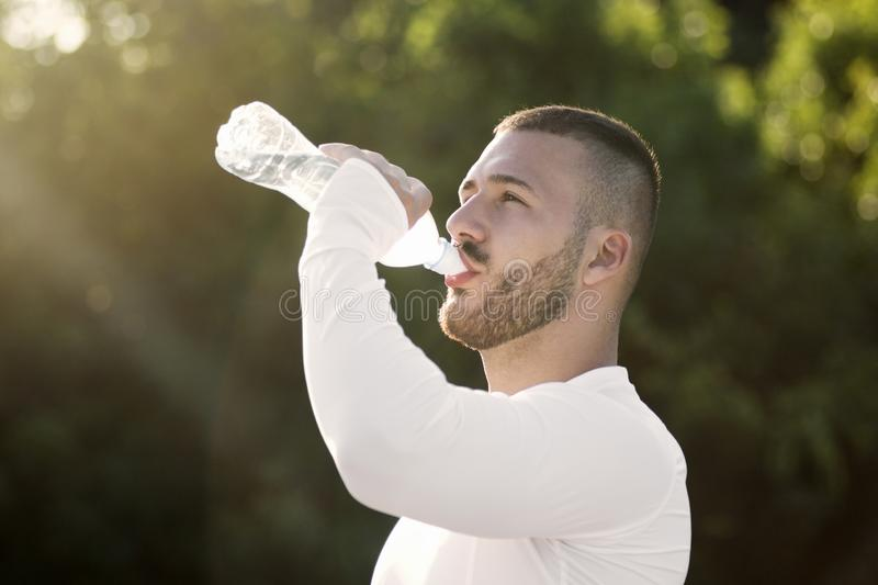 Young guy drinking water from bottle stock images