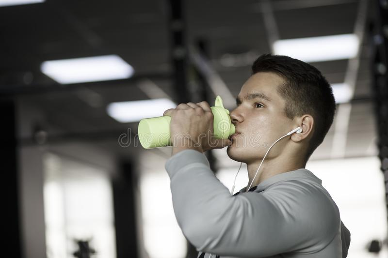 Young guy drinks from a shaker in gym stock photos