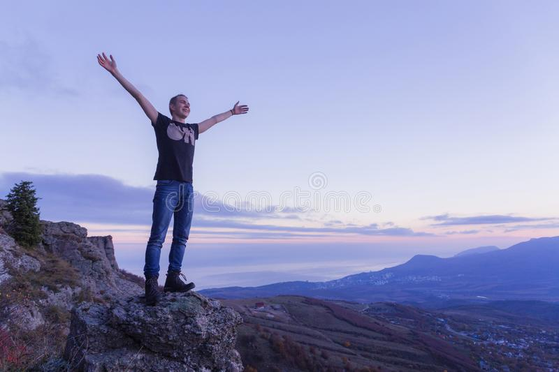 A young guy  is on the edge of a mountain abyss, spreading his arms toward the sky against of a purple sunset stock images