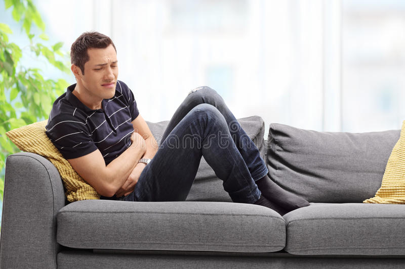 Young guy experiencing stomach ache. Young guy experiencing stomach pain seated on a couch at home stock photo